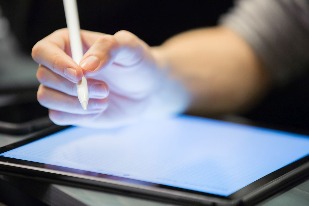 Hand writes with a pen on a tablet